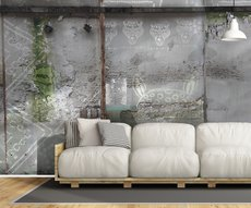 living room wall featuring a wallpaper with ethnic patterns embedded in a cement wall