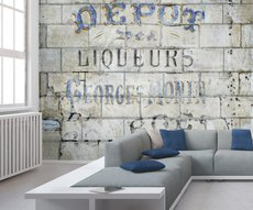 on the wall of this living room the wallpaper shows us an old advertisement of liquor painted on a stone wall